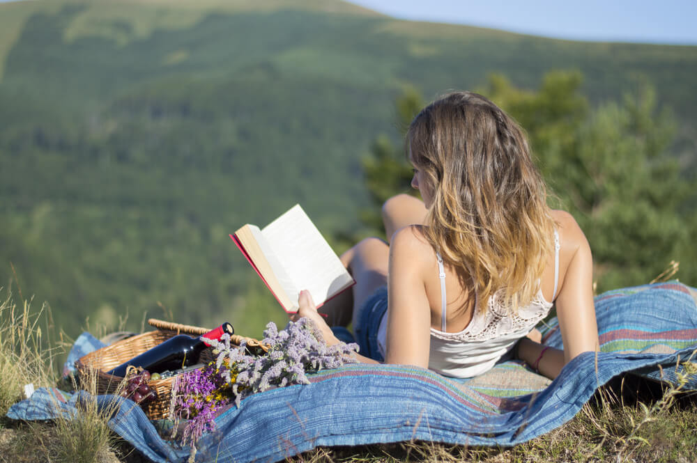 Best Cities for Introverts to Call Home | Girl Reading Book on Mountain | Where to Move