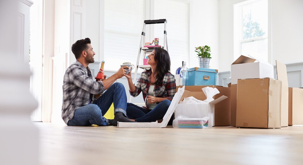 Moving Day Tips | Couple enjoying pizza and beer on the floor of their empty new apartment