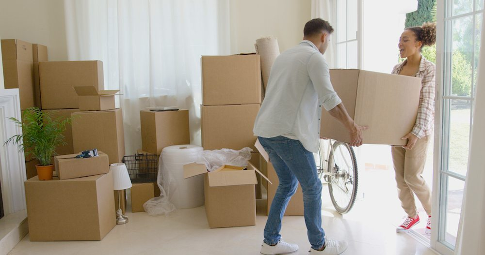 Moving Day Tips | Couple moving boxes into new apartment and stacking them in the corner