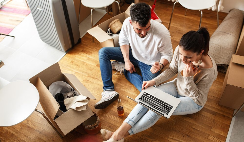 Moving Day Tips | Couple reviews their moving contract while surrounded by packed boxes